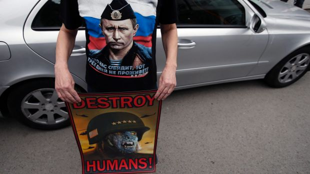 A man wearing a shirt showing a picture of Russian President Vladimir Putin holds an anti NATO poster during a protest ...