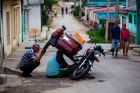 In this April 1, 2018 photo, men repair a motorcycle in the Vigia neighborhood of Santa Clara, Cuba. The man who is ...