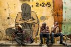 Men sell cooking oil and drink rum in front of a mural by a local street artist in Old Havana, March 26, 2018. Ra?l ...