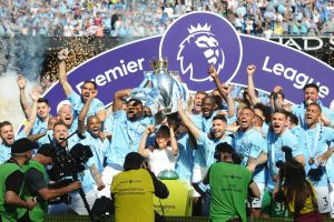 Manchester City players lift the English Premier League trophy after drawing with Huddersfield Town at Etihad Stadium on ...