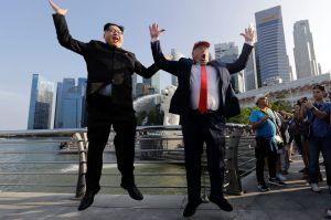 Kim Jong Un and Donald Trump impersonators, Howard X, left, and Dennis Alan, jump together as they pose for photographs ...