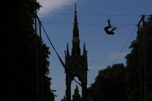 A man is silhouetted as he takes part in a Trapeze School near the Albert Memorial Statue in Kensington Gardens in ...