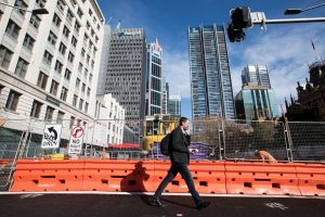 A man walks past the construction of the light rail at the intersection of George Street and Park Street, Sydney.