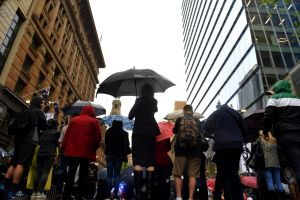 Office workers are seen during wet weather in Sydney, Thursday, October 4, 2018. (AAP Image/Mick Tsikas) NO ARCHIVING