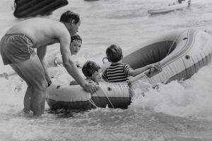 Brian Bell of Kaleen assists his sons Gregory 5 years (striped top) and Andre 4 years with their dinghy at Surf Beach.
