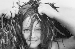 Fiona Game, 7, of Deakin covers her head with seaweed on Broulee Beach. 1986.