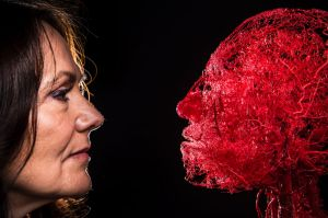Dr Angelina Whalley, wife of the inventor of plastination, Gunther von Hagens, with a plastinated head showing the ...