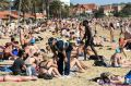 Police speak to beachgoers at St Kilda.