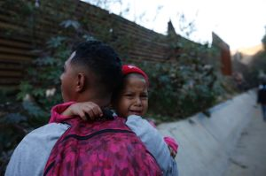 A Honduran migrant carries Jired Melendez, 4 years-old, as they try to cross over the U.S. border wall to San Diego, ...