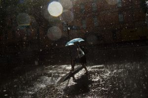 A person negotiates a flooded gutter in Pyrmont during a large storm in Sydney.