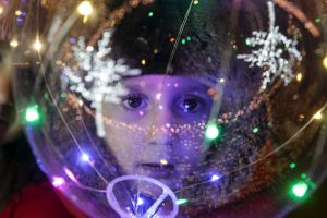 A boy looks through a Christmas tree decoration in downtown Grozny, the capital of Chechnya, Russia, illuminated for New ...