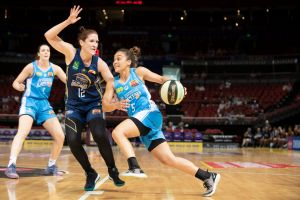 Canberra Capitals' Leilani Mitchell tries to drive past the Flames' Belinda Snell.