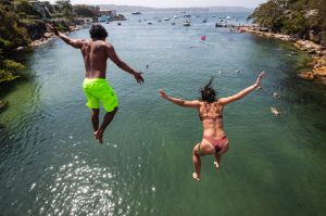 A couple jump into the water at Parlsey Bay in Vaucluse, Sydney on Sunday, January 27, 2019. Photo by Cole Bennetts