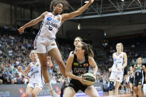 The Adelaide Lightning's Nia Coffey tries to defend against the Canberra Capitals' Keely Froling.