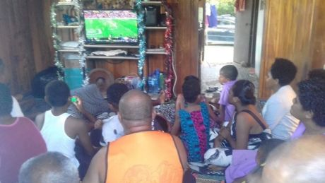 Packed house: Family and friends in Fiji gather to watch Maiko Sivo's NRL debut.