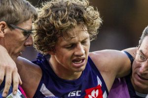 Out of action: Fremantle caption Nat Fyfe is escorted off the ground after a clash of heads, and didn't return to the game.