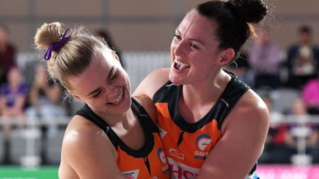 Giants Kiera Austin and Samantha Poolman celebrate their win over Queensland Firebirds on Sunday.