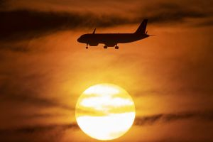 An aircraft approaches the airport as the sun sets in Frankfurt, Germany, Saturday, June 15, 2019. (AP Photo/Michael Probst)