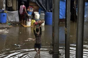A man holds a child high above his head as he wades through a waterlogged street following heavy rains in Mumbai, India, ...