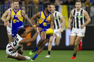 Willie Rioli slips the tackle of Collingwood's Isaac Quaynor.