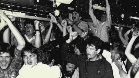 Patrons at the Middle Harbour Yacht Club go wild as Australia II crosses the line to win the America's Cup. The yacht ...