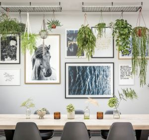 The dining area has an indoor garden. The dining table is from Amode, the Eames chairs from Vitra, and the wall frame ...