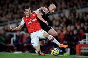 Arsenal's Granit Xhaka tussles with Brighton's Aaron Mooy.