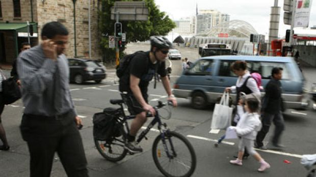 Follow the rules ... pedestrians and a cyclist share the road on a city street yesterday.