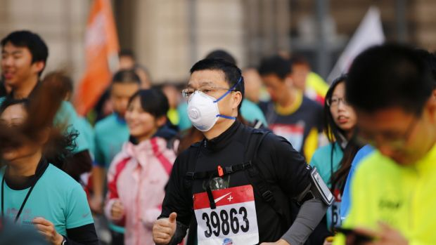 A participant wears a face mask as he competes in the Shanghai International Marathon. The US consulate stated that the ...