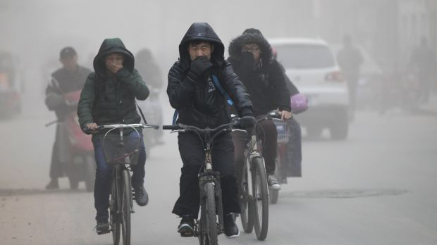 Public concerns: Residents cover their face from dust as they ride their bicycles along a street on a hazy day in ...