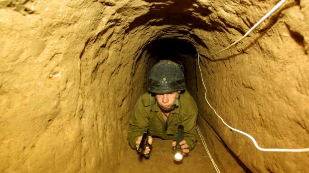 Fighting underground: An Israeli soldier crawls through a tunnel built by Palestininans from the Gaza Strip town of ...