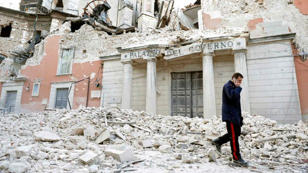 A police officer walks past ruined government buildings in L'Aquila in April 2009.