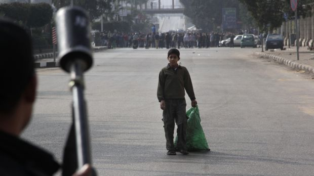 Divided nation: A boy looks at security forces as they try to disperse Mursi supporters in Cairo on Friday.