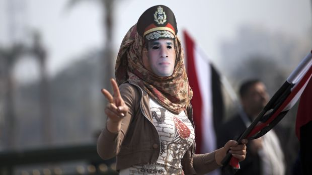 A woman wears a mask depicting Field Marshal Sisi.