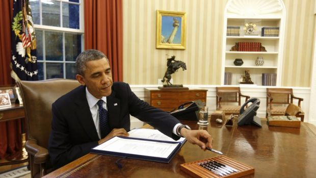 US President Barack Obama reaches for a pen as he signs a bill in the Oval Office in 2013.