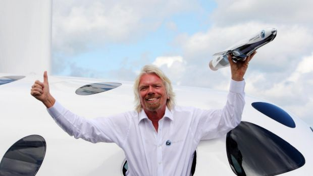 Sir Richard Branson poses with his Virgin Galactic Space craft at Britain's Farnborough International Airshow in 2012.