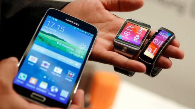 The new Samsung Galaxy S5 smartphone, left, with the Gear 2 smartwatch, centre, and Gear Fit fitness band. Samsung has ...