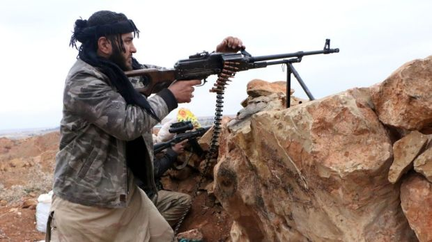 A rebel fighter fires towards pro-regime forces during clashes in Sheikh Najar area of the restive Syrian city of Aleppo ...
