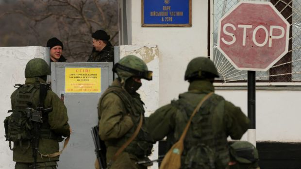 Standoff: Surrounded by unidentified Russian soldiers, Ukrainian marines talk behind a wall at their base in Perevalnoye.