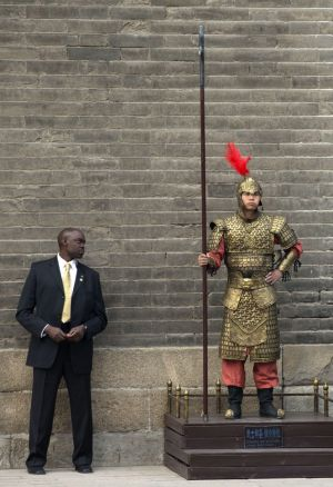 Vigilant: A US Secret Service officer checks a Chinese performer dressed as an ancient warrior as US first lady Michelle ...