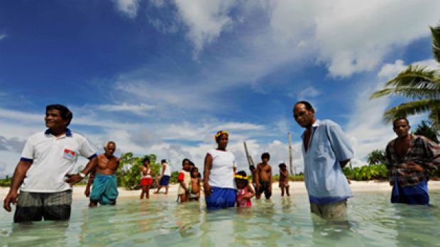 Villagers on the island of Abaiang stand in the sea where their homes used to be.