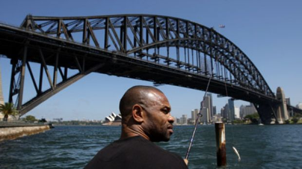 Gone fishin' . . . American boxing great Roy Jones jnr takes time out from training to wet a line on the harbour ...