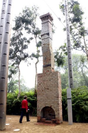 Curator Liza Dale-Hallett stands beside the rebuilt chimney at the Melbourne Museum.