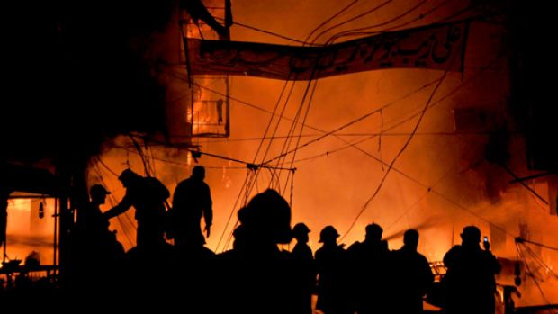 Pakistani firefighters extinguish fire after twin bomb blasts in Lahore.