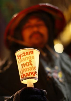 """An activist of the environmental group """"La Via Campesina"""" holds a cup with a candle in central Copenhagen."""