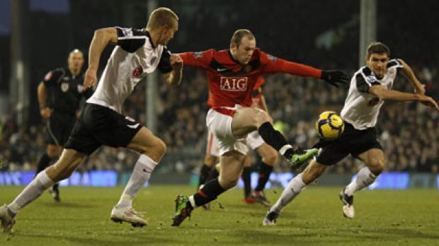 Closing in...Fulham's Brede Hangeland and Aaron Hughes keep tabs in United's Wayne Rooney during their Premier League ...