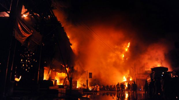 Suicide blast ... angry protesters set fire to a market after a  bomb attack in Karachi during the religious festival Ashura.