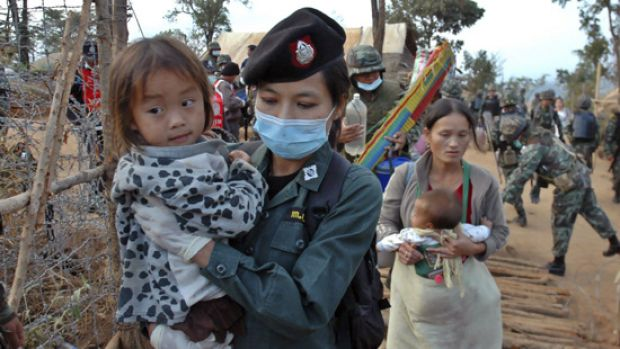 A Thai policewoman holds a Hmong child refugee at the Ban Huay Nam Khao camp in Phetchabun province.