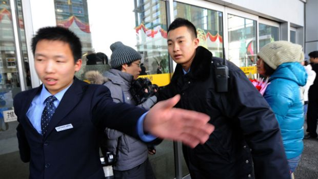 Cyber attack ... guards try to remove journalists as a woman delivers flowers to the Google office in Beijing.