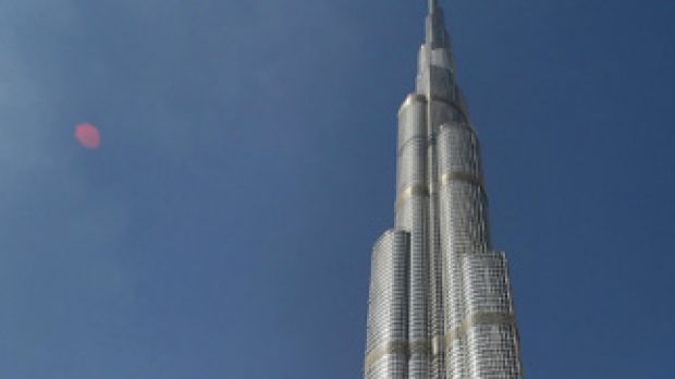 Emirati men walk past Burj Dubai, the world's tallest tower, in the Gulf emirate nation.  In an ambitious move, US ...